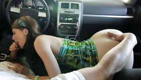 Whore is kneeling in the car while sucking penis